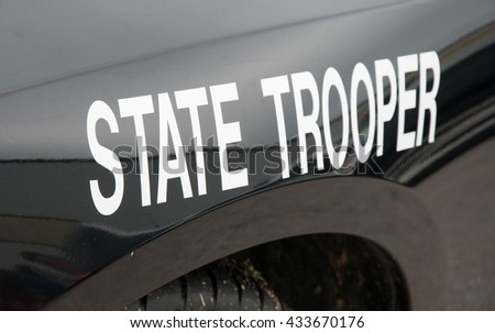 White state trooper -decal on a black law enforcement vehicle