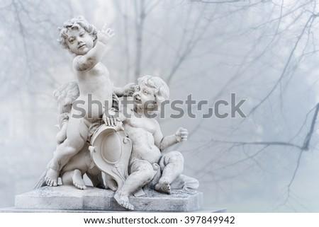White statue of angel boys in park of city. Vienna, Austria. Europe travel. - stock photo