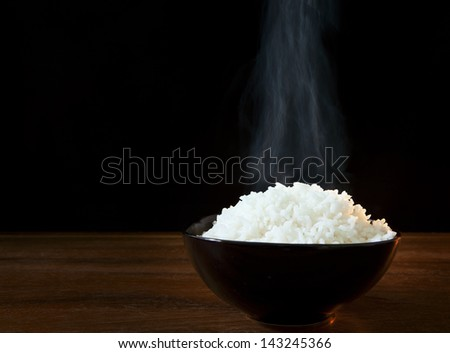 white steam rice in black ceramic bowl with smoke on black use for food topic - stock photo