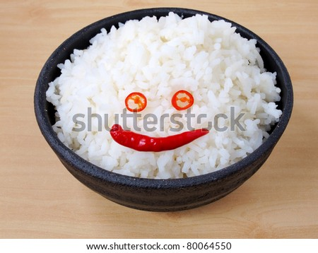 White steamed jasmine rice with fresh smiling chilli in black ceramic bowl - stock photo
