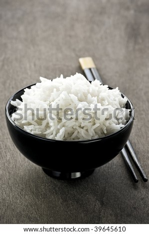 White steamed rice in asian bowl with wooden chopsticks - stock photo