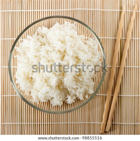 white steamed rice with sticks on bamboo background - stock photo