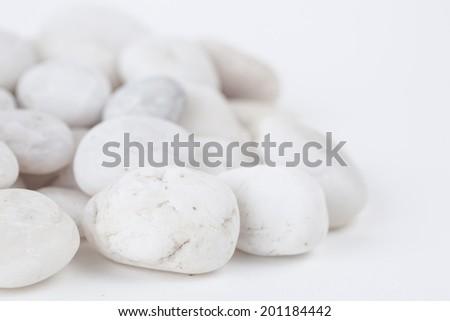 White stone on white paper background - stock photo