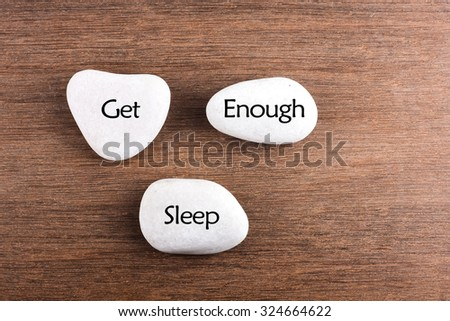 White stones with Get enough sleep word on wooden background - stock photo