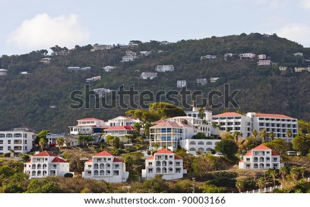 White stucco vacation homes with red tile roofs on a tropical hillside - stock photo