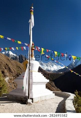 White stupa and prayer flags near Namche Bazar, mount Everest, Lhotse and Ama Dablam, way to Everest base camp, Khumbu valley, Solukhumbu, Sagarmatha national park, Nepal - stock photo