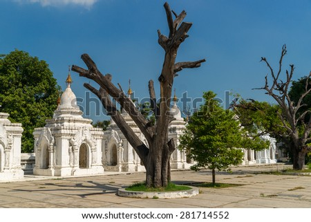 White stupas of the Kuthodaw Pagoda in Mandalay. In total 729  stupas with a marble slab inscribed on both sides surround the main pagoda, thus it is believed to be the largest book in the world. - stock photo