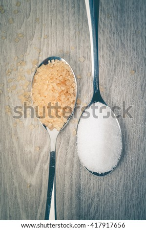 White sugar and brown sugar and a spoon on a wooden floor. - stock photo