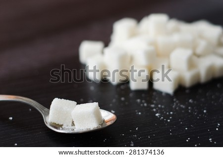 White sugar cubes piled in a heap on the black desk with spoon - stock photo