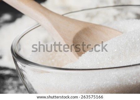 white sugar in a glass bowl and wooden spoon, close up