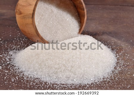 White sugar in a wooden bowl - stock photo