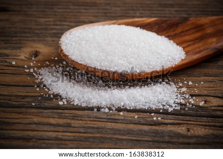 White sugar in a wooden spoon - stock photo