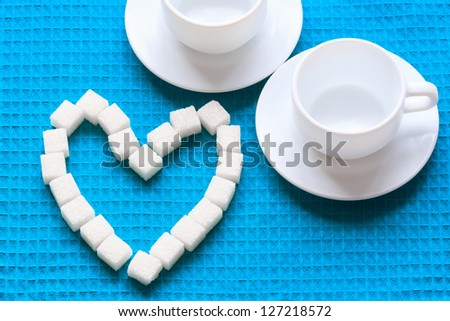 White Sugar in heart shape on blue napkin - stock photo