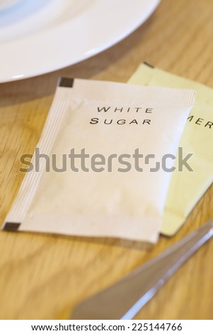White sugar paper pack beside a cup of coffee - stock photo