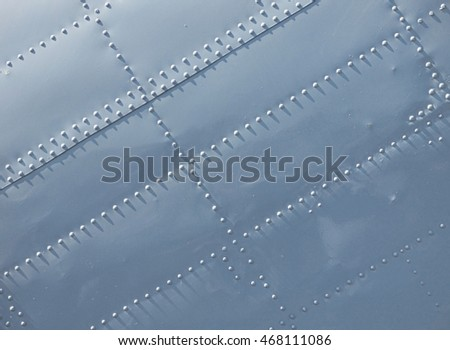 White surface with diagonal lines of screw heads. High contrast lighting. Metal texture.  Industrial steel background with place for text. Abstract technology wallpaper with diagonal dotted structure.