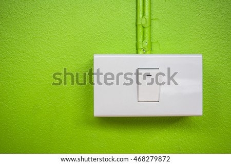 White switch on green cement wall