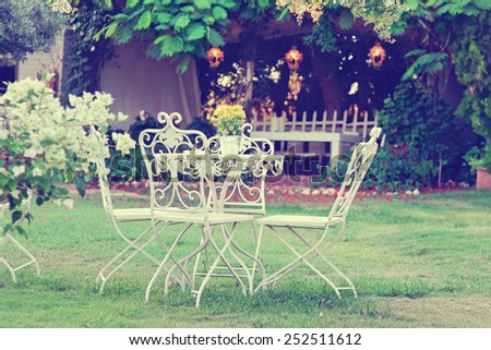 White table and chairs in beautiful garden. Vintage style pictures. - stock photo