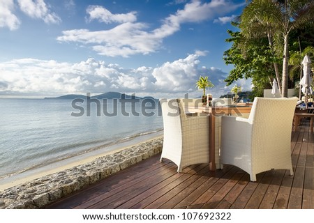 White table with chairs on decking, by the beach - stock photo