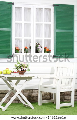 White table with fruits and flowers, chair near house with window with shutters. - stock photo