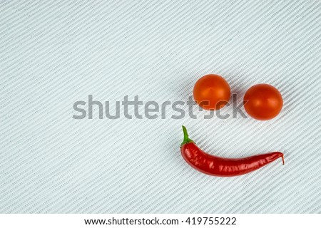 White table with red chilli and tomatoes - stock photo