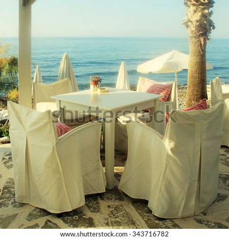 White tables and chairs in greek cafe by the sea coast, Crete, Greece. Sunset light. Square toned image, instagram effect - stock photo