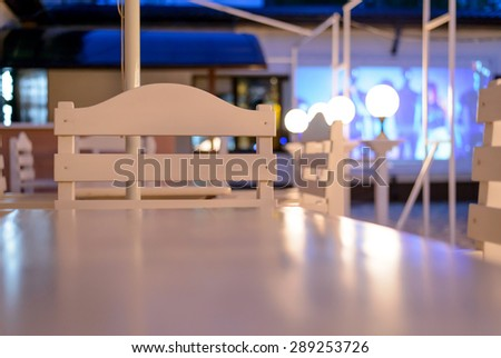 White Tables and Chairs on Outdoor Patio at Night, View of Empty Restaurant or Club Patio from Across Shiny Clean Table Surface - stock photo