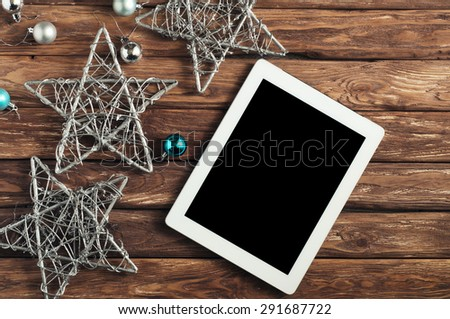 White tablet computer  on a wooden table with with Christmas toys and stars. view top  - stock photo