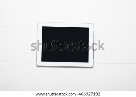 White Tablet. Tablet pc on white wooden table - stock photo