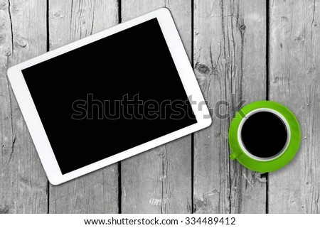 White tablet with a green coffee cup on old wooden table. Blank screen with space for copy. Concept the coffee break with the use of the tablet. - stock photo