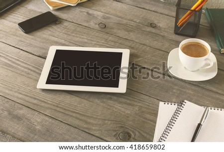 White tablet with blank screen on wooden table in a home office