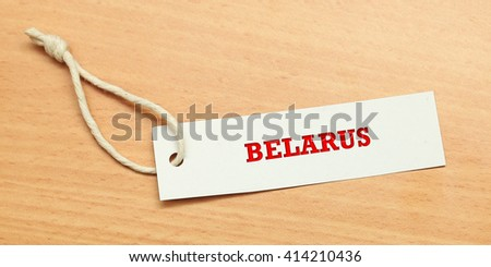 White tag on wooden background with word Belarus