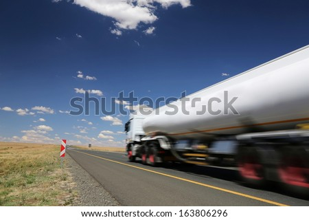 White tanker truck transporting fuel along the tar highway - stock photo
