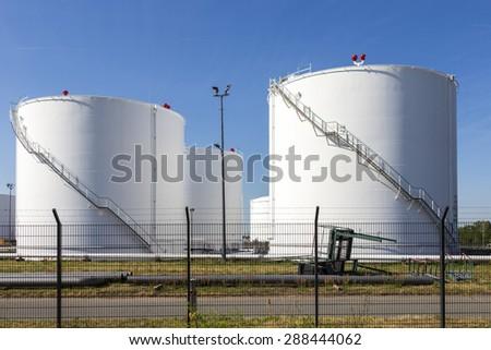 white tanks in tank farm with iron staircase under blue sky - stock photo
