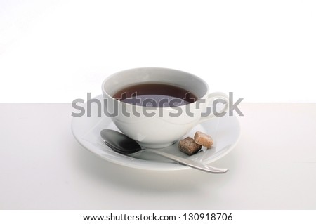 White tea cup and saucer with sugar and a tea spoon