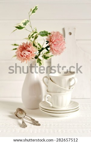 white tea cups and a vase of flowers on a light wooden surface, vintage style - stock photo