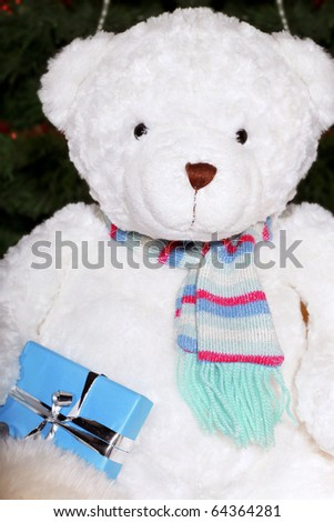White teddy bear holding a present and sitting at the Christmas tree
