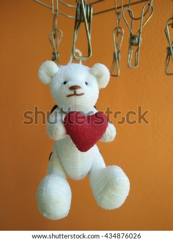 White teddy bear holding a red heart  hanging on clothespin orange background - stock photo
