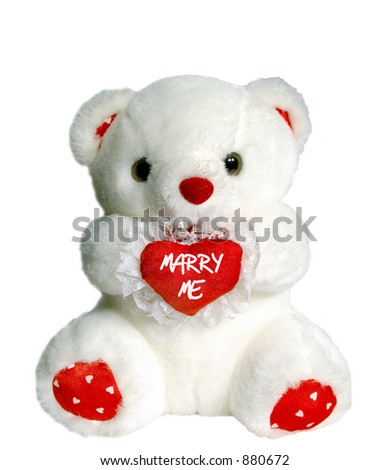 "White teddy bear holding heart pillow that says ""marry me"""