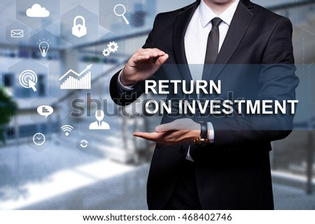 "White text with icon ""Return On Investment"" in the hands of a businessman. Business concept. Internet concept."