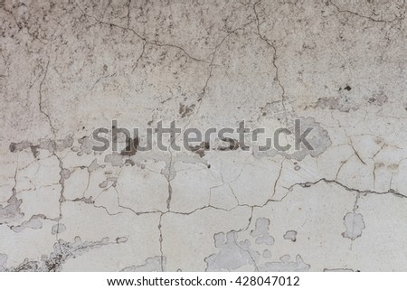 White texture of old wall with cracks. Cracked surface of the wall or the floor at home with stains and peeling paint