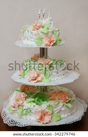 White three tier wedding cake decorated flowers with two swans top. - stock photo