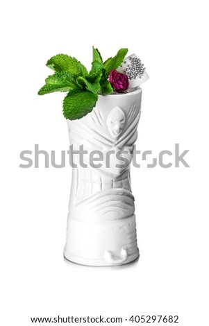 White tiki mug decorated with rose, mint leaves and bridal veil  - stock photo