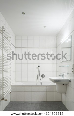White tiled bathroom with toilet, bathtub, sink and mirror - stock photo