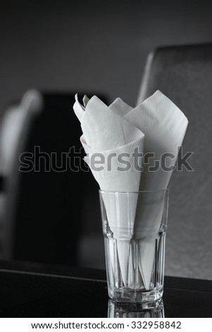 White tissue papers in glass on black leather chair background - stock photo
