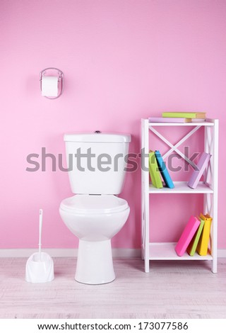 White toilet bowl and stand with books, on color wall background - stock photo