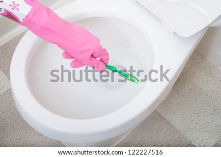 White toilet bowl cleaning wearing gloves using a toothbrush or sponge scrubby - stock photo