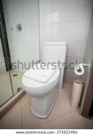 White toilet in a bathroom tiled interior  - stock photo