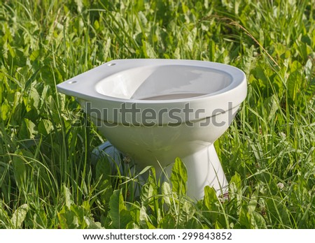 White toilet on a field. - stock photo