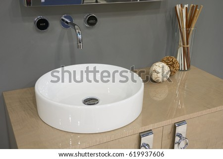 White top ceramic washbasin with glossy metal mixer mounted to the wall