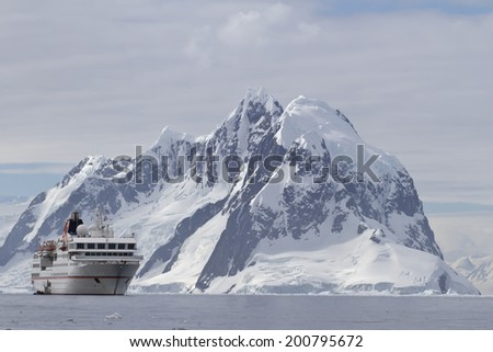 White tourist ship a summer day on a background of mountains of the Antarctic Peninsula - stock photo